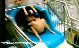 Asian couple gets a quick fuck on the waterslide before going down it